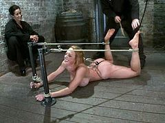 Sexy blonde girl lies on the floor being tied up in acrobatic pose to a bondage device. Isis Love comes up to her and fingers her pussy.