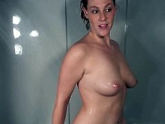 Sexy brunette is taking a shower without taking off her T-shirt