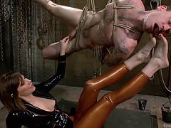 This sexy mistress called Madeline, has her slave tied up in rope bondage and hung from the ceiling. He is ready to be tortured. She spins him around with her feet and make him suck on, & sniff her pretty toes. He's not the only one with feet in his mouth. Madeline sticks her feet in the faces of women, as well.