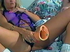 A blonde and a brunette have lesbian fun in a bedroom. They finger and then toy each others hairy pussies.