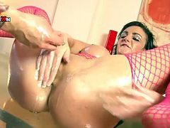 This sex-starved hottie in pink fishnet stockings will never miss a chance fora good, hard fucking. She makes her lover fist her oiled snatch. Then he fucks her juicy muff in missionary position.