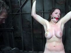 Brown-haired girl with juicy tits gets gagged and tied up. Later on she sucks big dildo and gets whipped painfully.