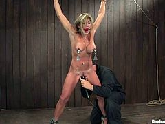 Bosomy blonde milf Felony is having fun with some dude in a cellar. She lets the guy put her into chains and then gets her tits decorated with weights and her snatch rubbed with a chain.
