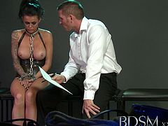A clanging sound can be heard as sub Stacey's cast iron shackles which attach her neck, wrist and ankles together move. She waits impatiently for her Master, she should know better than to have this attitude as when Master Rose comes in it's immediately evident that he has no tolerance for her back chatting and the sound of her whiny voice and neither is he impressed by her tattooed skin and tiny black shoes. After the signing of the Slavery Contract and the repeat of the safe word sub Stacey was forded to the ground and made to open her legs as the heavy chains from her shackles banged agains