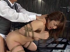 This cutie gets locked in a cage where she has her nipples clamped and she's tied up with ropes. Fucking hot stuff, dude!