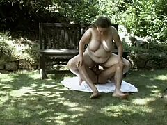 Obese brown-haired mom Dandi is getting naughty with some guy outdoors. She gets fondled by the dude and then they have sex in side-by-side and reverse cowgirl positions.
