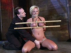 Curvaceous blonde chick gets her tits tortured and covered with hot wax. Later on the master shoves a hook in her ass and toys the pussy.