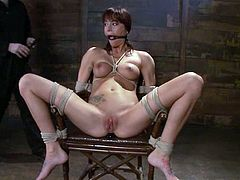 Cute dark-haired chick Gia Dimarco gets bound by some guy in a basement. The man rubs Gia's vag with a dildo and then attaches weights to her nice tits and suspends the hottie.