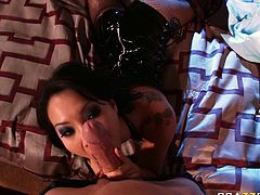 Raven haired Asian babe Asa Akira looks torrid in her fishnet pantyhose and leather corset. She chokes on huge dick sucking it balls deep and then pets her shaved snapper with her hands.