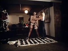 Desiree Cousteau is bounded by her arms to the ceiling almost naked. Bitch gets her wet hairy pussy fucked from behind. Later brown haired slut gives blowjob.