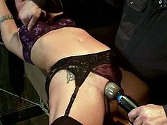 Brunette girl in lingerie and stockings gets tied up in dark room. Then the master fixes clothespins to her tits and toys the pussy with a vibrator.