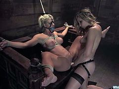 Holly Heart and Maitresse Madeline are having BDSM fun in a basement. The dominant blonde binds her GF and tortures the hottie before fisting her pussy.