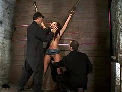 Slender brunette babe in a miniskirt gets tied to a wall. Then her masters fix claws to the nipples and toy her juicy vagina.