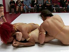 A redhead, a blonde and a girl with black hair are in the ring together. First the blonde and black haired girl fight and flop around the ring. The redhead is tagged in and the blonde is pinned down by the other two girls.