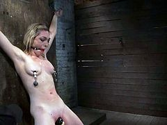 Horny blonde girl gets tied to a wall and gagged. Then the master fixes clothespins to her nipples and toys the pussy.