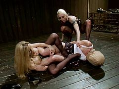 Two blond bitches trap this slave in the yoke bar
