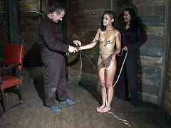 Skinny brunette girl gets tied up and undressed by a couple. After that her masters fix pumps to her titties.
