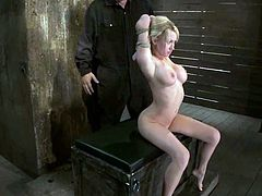 Superb blonde girl lies down on a wooden chest and gets tied up. Then some guy fingers her hot pussy and whips her feet.