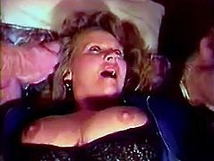 Anna Lisa sits on a bed and sucks two penises. Then she lifts her dress up and gets fucked from behind. After that two guy cum on Anna's face and tits.