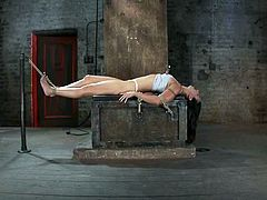 Tied up brunette girl lies on a wooden box. The master whips her feet and then tortures tits with claws. Later on he also toys her vagina with a vibrator.