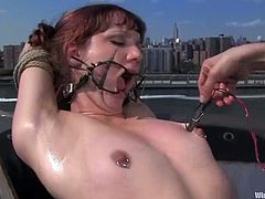 Kinky bitch Betty Baphomet is playing BDSM games with Nadia Styles on a yacht. Nadia binds Betty and fingers her cunt and then attaches many wires to her shaved pussy.