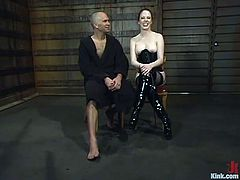 Kinky girl in high boots and a corset ties a bald guy with straps. She tortures his dick and balls. After that she toys him with a strap-on from behind.