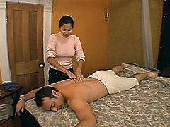 Hot Asian milf is trying to please some man indoors. She oils and massages his body passionately and then shows her handjob skills to the dude.