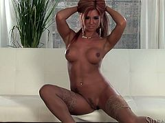Hot blonde chick Ashley Bulgari wearing stockings is having fun in the living room. She takes her bra and lace panties off and demonstrates her big fake tits and nice pussy.
