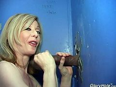 Hot blonde mom Nina Hartley is getting naughty with a black dude in amazing gloryhole action. She sucks the BBC through the hole in the wall ad enjoys herself.