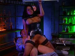 Superb brunette babe in ripped fishnets and a leather corset blows a dick excitedly. After that she lies down on a bar counter and gets fucked hard.
