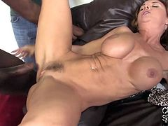 Get a boner watching this redhead cougar, with a nice ass and big fake tits, while she gets fucked by two big black cocks in a reality video.