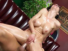 Touch yourself watching this brunette cougar, with big fake jugs and a smooth cunt, while she gets drilled hard over a couch by a steamy fellow.