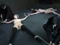 Two busty blondes take their clothes off and lie down on the floor. Then they get tied up by their masters. Later on these chicks get their pussies toyed and fingered.