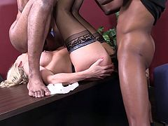 Simone called these two guys into her office and ended up sprawled across her desk with them slamming that big cock deep inside her.