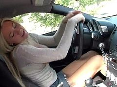 Share this with your friends! A blonde, with giant natural gazongas wearing a miniskirt, exposes her breasts while she has her hands on the wheel.