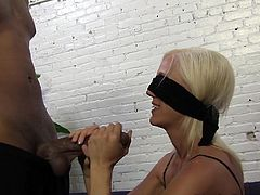 Sexy blonde white pornstar Kacey Villainess puts on a blindfold and sucks some black cock backstage at a porn movie shoot.