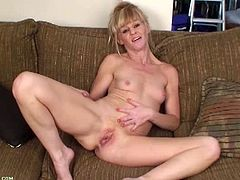 Inviting slender blondy slips out of her dress and reveals her sexy slim body. She sits down on a couch and rubs her trimmed pussy before fucking herself with her fingers.