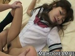 Megumi Kitigawa is a Japanese schoolgirl. She plays with a vibrator to warm up before sex. Then, she slides her man's cock inside her hairy pussy and rides him.