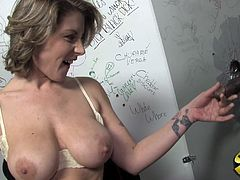 Check this short haired blonde, with huge fake tits wearing a thong, while she goes hardcore with an unknown dick from a gloryhole.