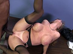 Get excited watching this redhead cougar, with huge fake tits wearing stockings, while she goes hardcore over a table and reaches an orgasm!
