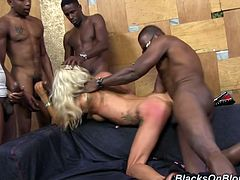 Naughty blonde girl with fake tits drops to her knees and gives a blowjob to three guys. Then this slutty chick takes rough pussy fucking.