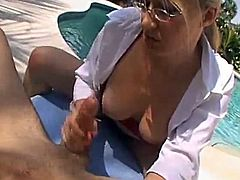 Kinky blonde milf wearing a bra and glasses is having fun with some dude on the poolside. She strokes and rubs his dick and they both enjoy it much.
