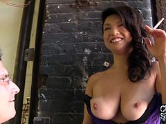 Backstage at her shoot, Mia pulls out her amazing tits and lets a couple of guys nuzzle between them and suck on her nipples.