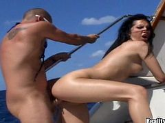 Slutty brunette girl in a bikini gets her ass massaged. She gets so damn horny that has sex with two guys on a boat. She sucks big dicks and gets her soaking pussy fucked like never before.