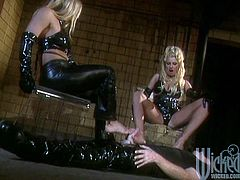 Brittany Andrews and Serenity wearing latex costumes are having fun with some dude in a basement. They pet the guy and then jump on his wang ardently.