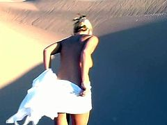 A sweet girl in a white dress lies on sand. She shows her juicy boobs and booty. Later on she takes the dress off and walks around.
