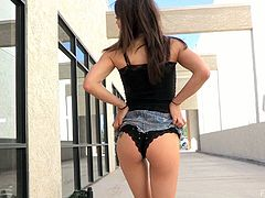 A beautiful girl lifts her jeans skirt and sits down on a pavement. This hottie fingers her nice pussy and then stuffs it with panties.