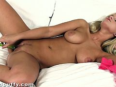 A lovely blonde in pink lingerie toys her pussy with a thin dildo