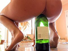 Sexy blonde chick in a black dress and high heels masturbates in a kitchen. She lifts the dress up and pushes the wine bottle deep in her smooth pussy.