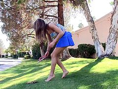 Brown-haired chick Mali is getting naughty in the garden. She demonstrates her muscles and then takes her dress off and demonstrates her boobs for the camera.